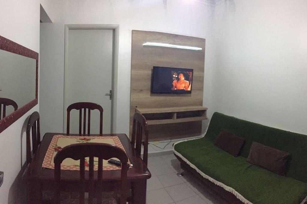 Sala com TV, sofá cama e Mesa de Jantar.