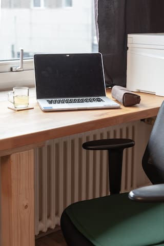 A desk just beside the window where you can work using your laptop, documents, books and more.