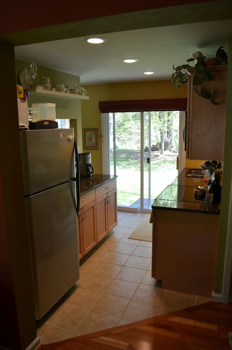 Open, walk-thru kitchen leads to backyard and grill.