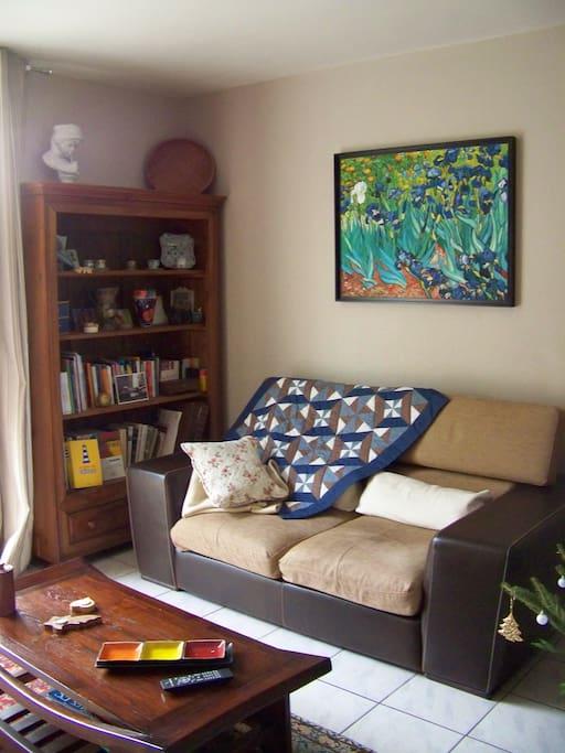 Salon équipé d'un canapé cuir et tissu, de trois fauteuils, d'une télévision sur son meuble bas, d'une chaîne Hi Fi . Pièce donnant sur jardin coté Est et possédant une baie vitrée.