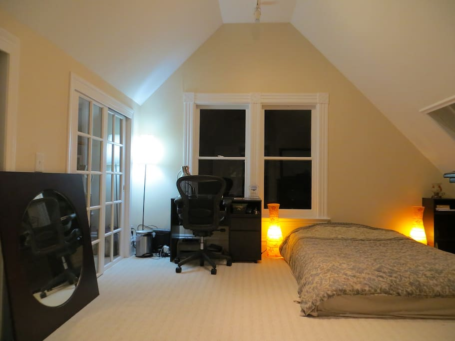 Large room with vaulted ceiling includes comfortable bed as well as work-space.