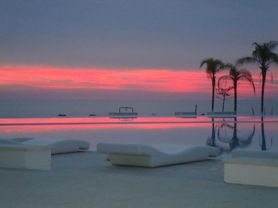 Sunset by the pool which seems to endlessly pour into the warm beach water.