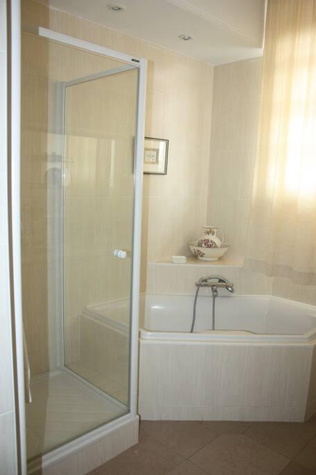 Salle de Bain avec baignoire d'angle, douche et double vasque.
