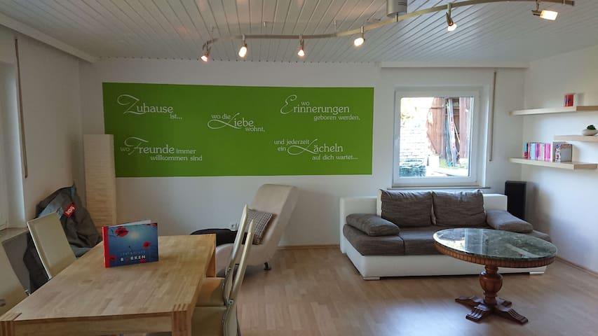 Wohnzimmer mit Esstisch, Relaxliege, Sitzsack und Schlafsofa, sowie zwei Fenster für einen hellen Raum.