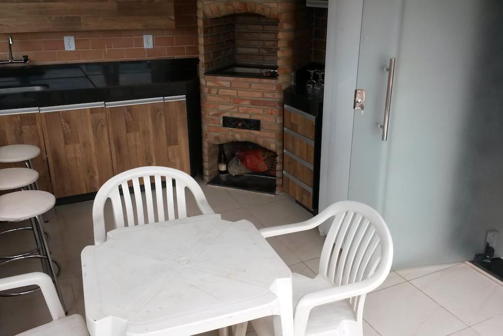Área externa com mesa e 4 cadeiras, 3 banquetas, pia, churrasqueira, geladeira, além de armários.