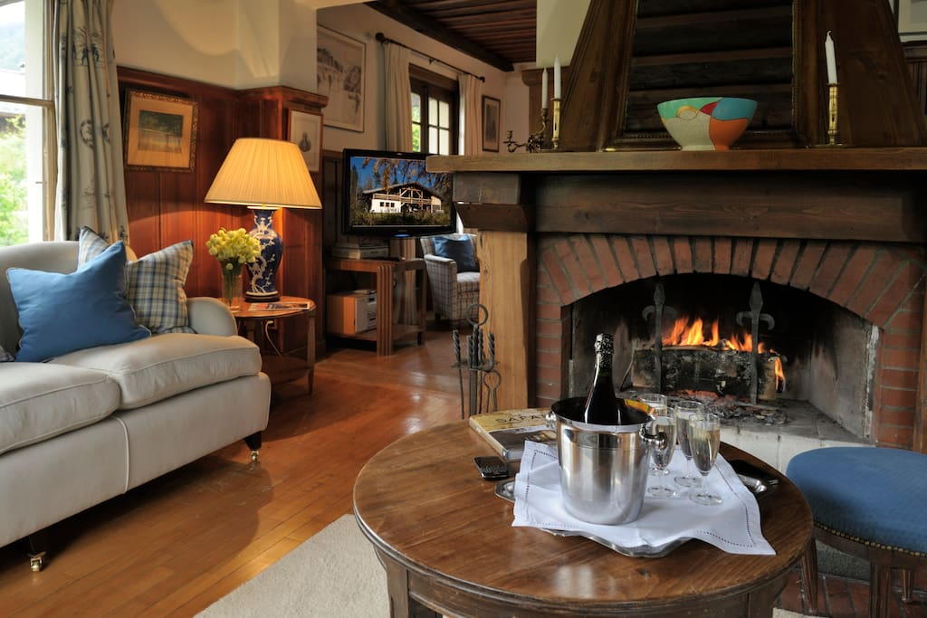Sitting room and open fire, large flat screen tv in one area.  Doors to the garden to enjoy the view of Mt Blanc.