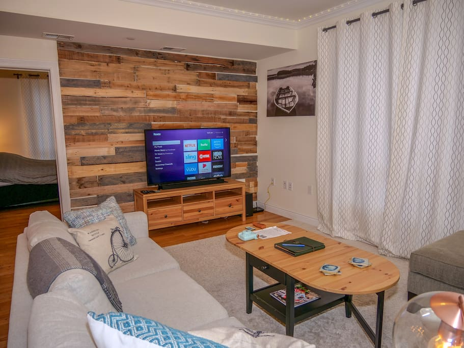 LOVELY wooden pallet wall with 55' Flatscreen TV, including Samsung soundbar and subwoofer. Television includes Netflix, Amazon Prime, and YouTube.