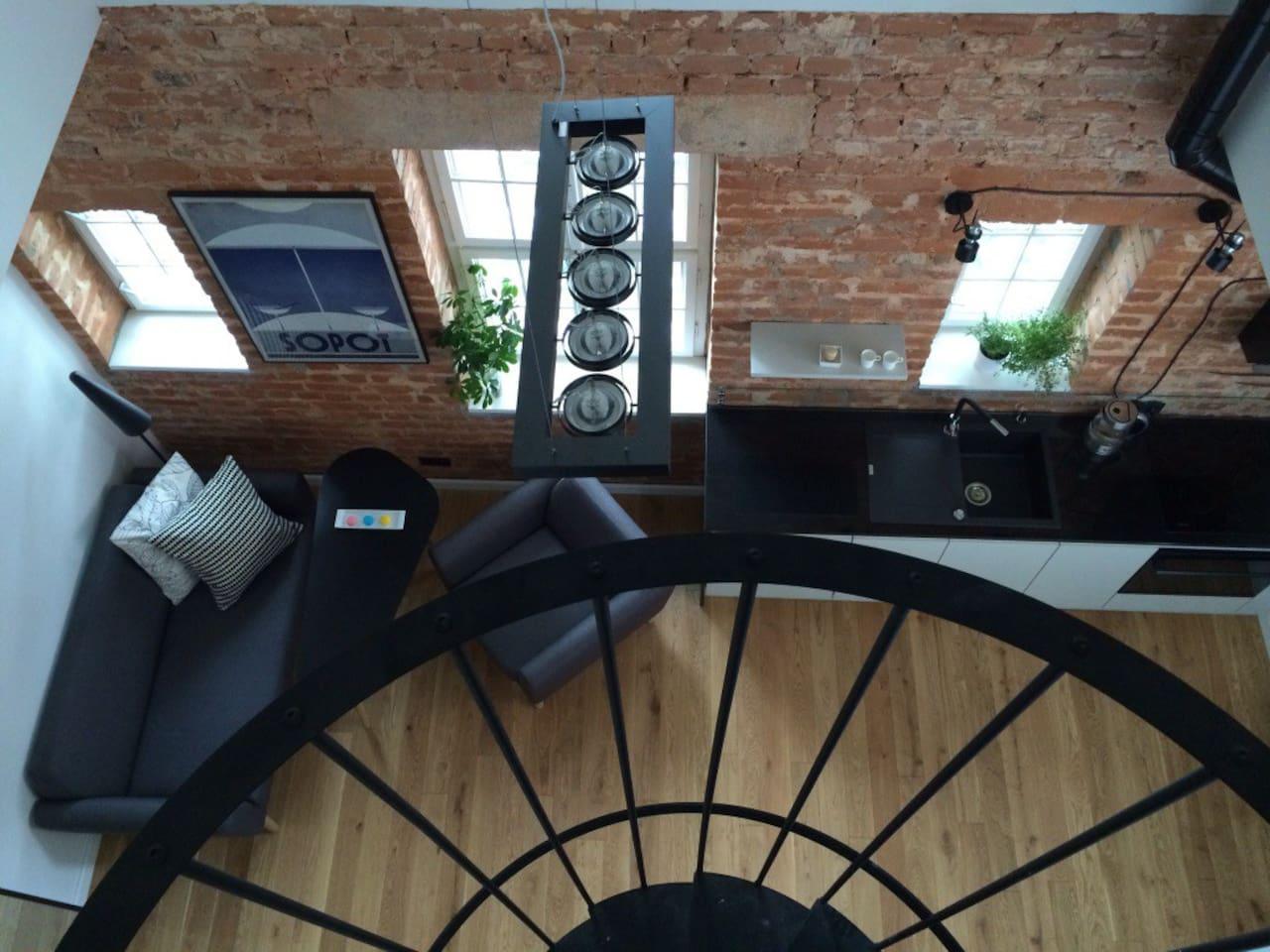 Living room with kitchen, oak floor, original wooden windows, exposed brick wall.
