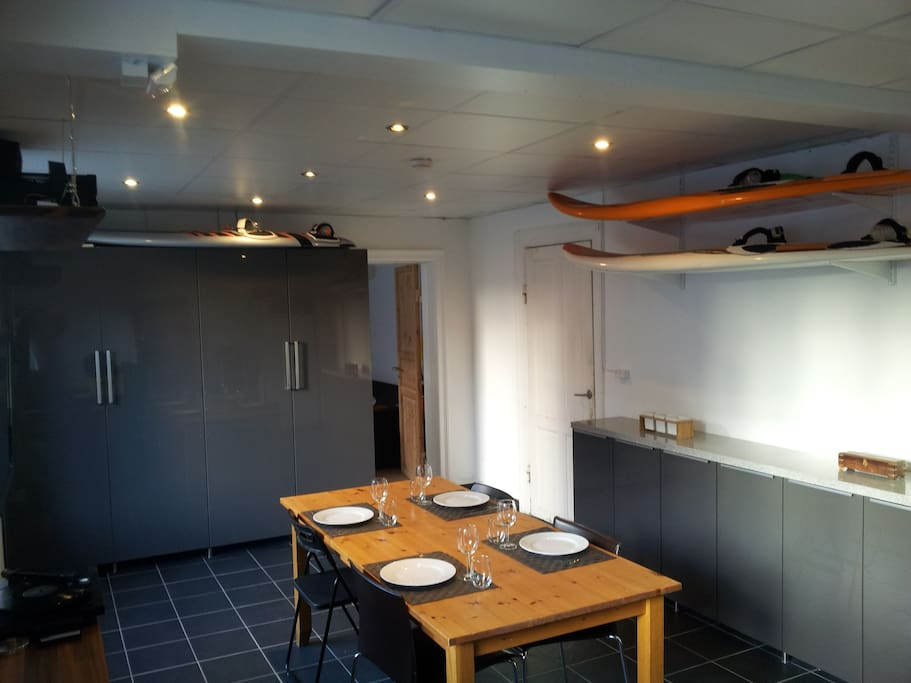 Large dining room with stereo, TV and surfboards.