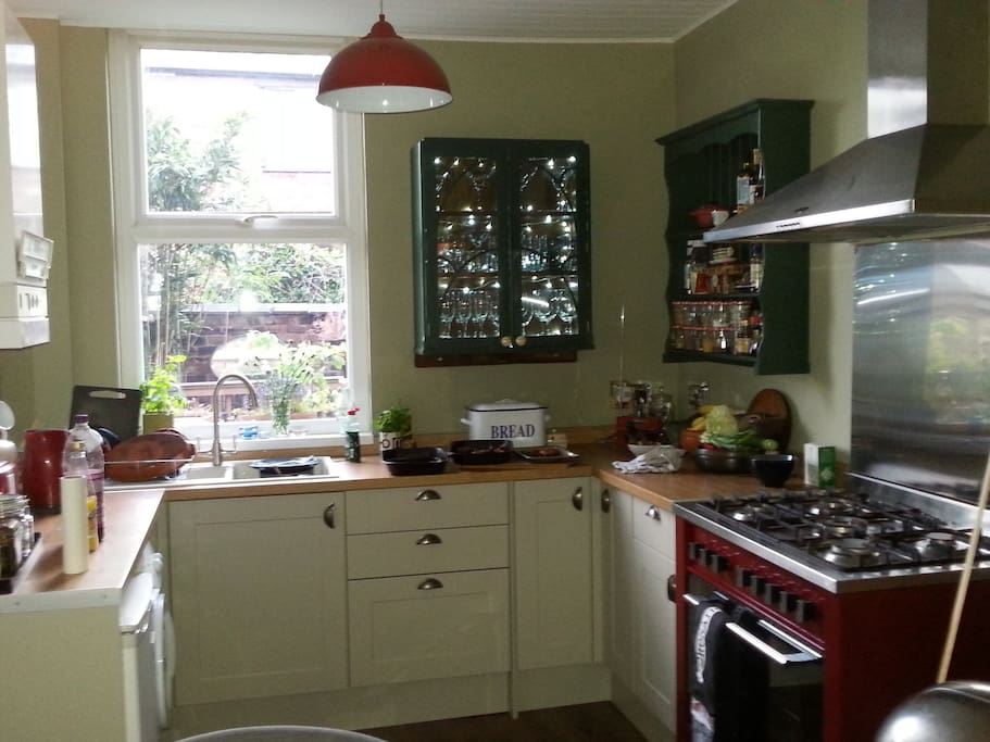 Large kitchen overlooking the garden with large cooker, washing machine, kitchen table and pantry.