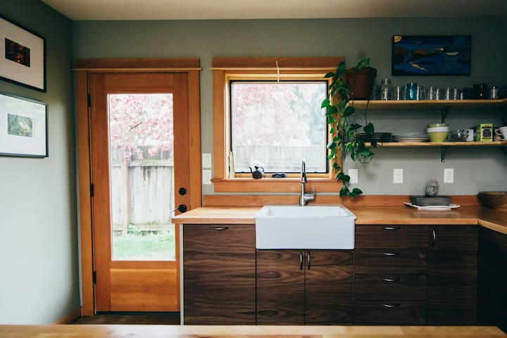 farmhouse sink, walnut cabinets, big gas range and island and more