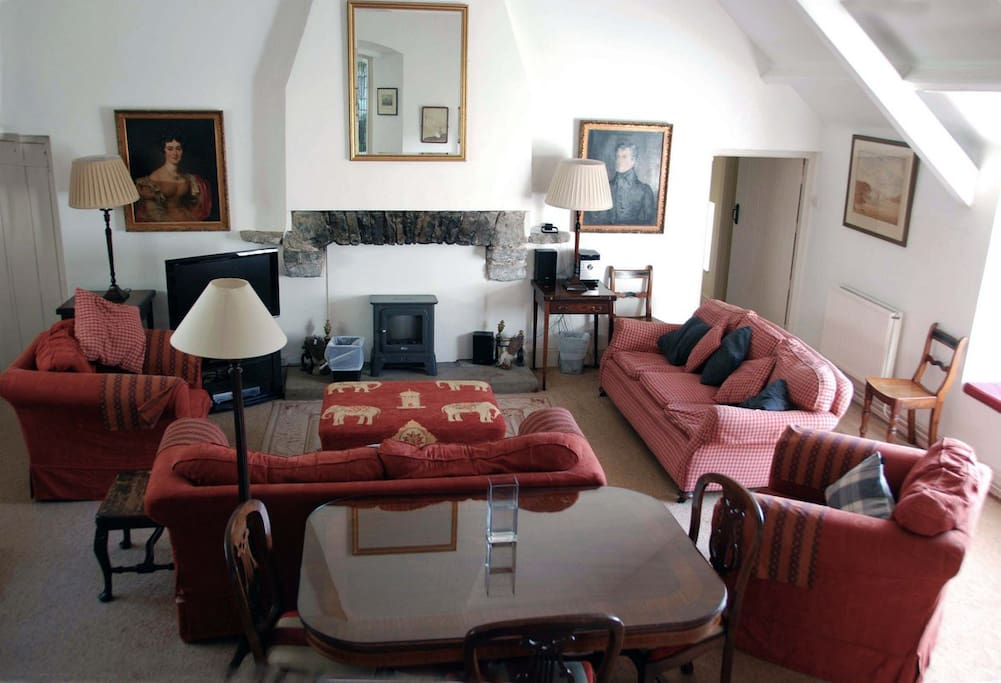 A spacious sitting room with windows looking  into the castle garden.