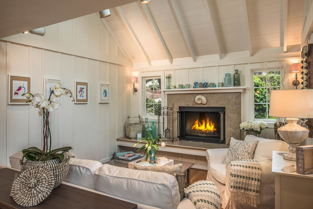 Living room with wood-burning fireplace and gas kindler.