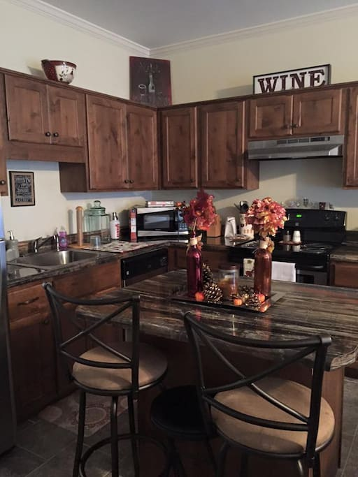 Open concept kitchen with bar stools- Stainless Steal Appliances- over-microwave-wine cooler