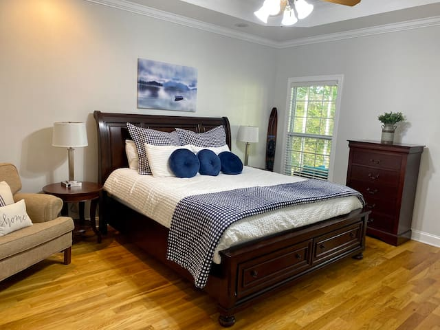Master Bedroom with super comfy King sized bed, view of the lake, and additional door leading to our cozy screened porch.