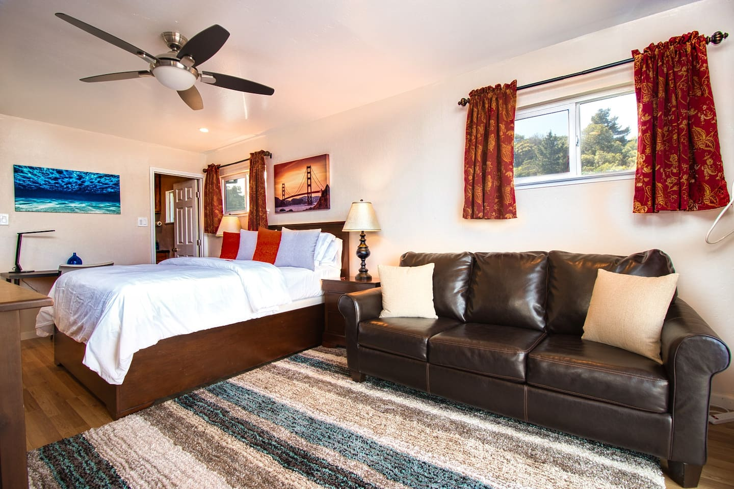 Gorgeous studio with luxurious queen bed, tons of natural light, large sofa bed and colorful art.