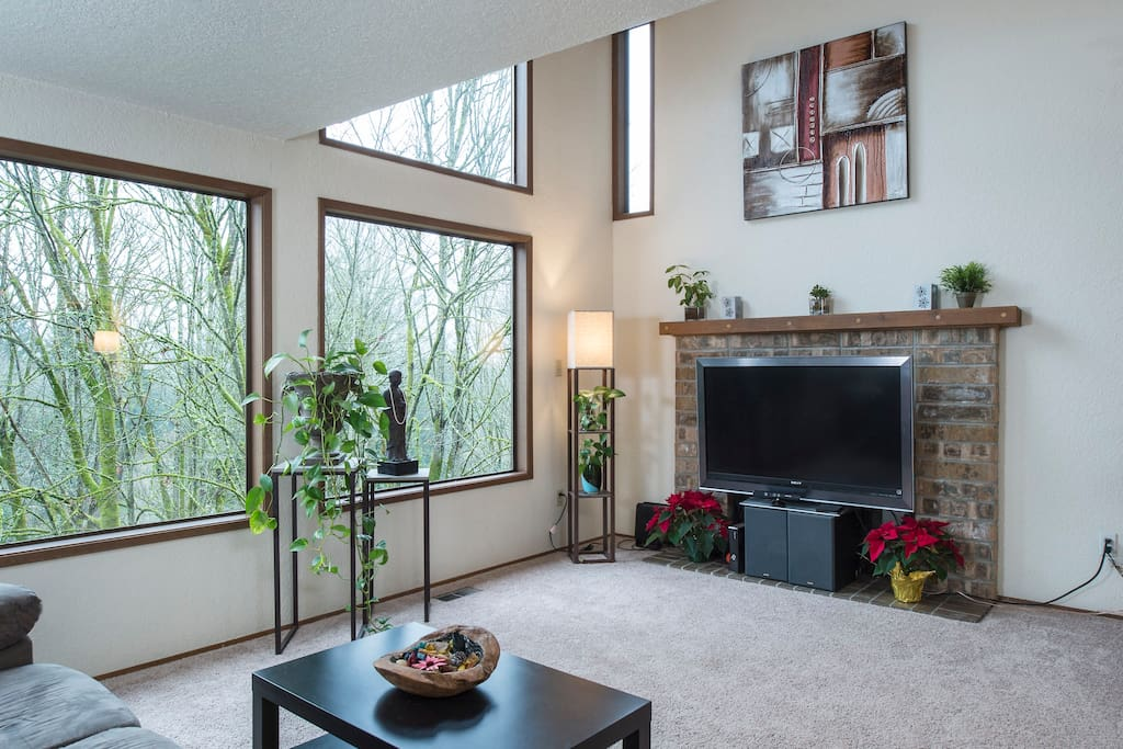 Main living room with large windows to welcome sunshine and forest in