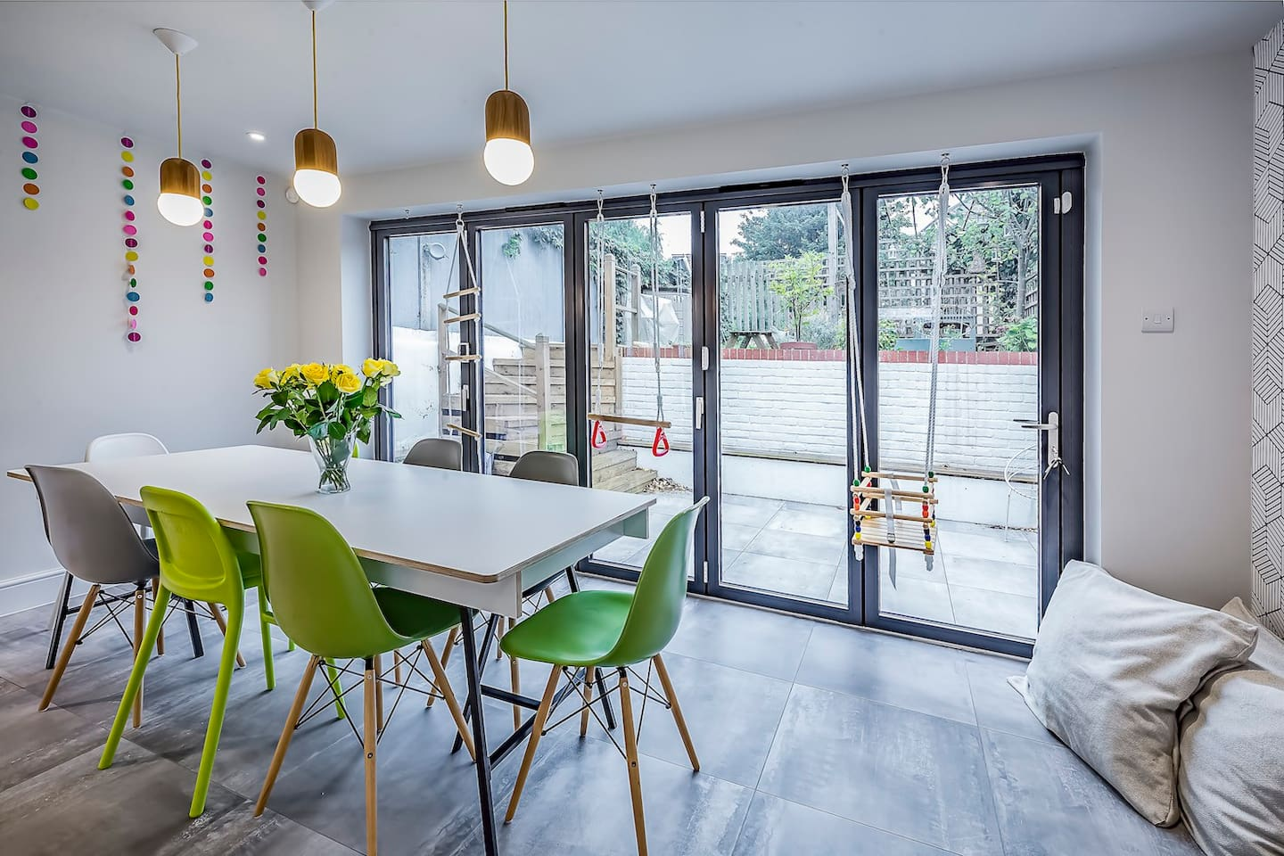 Kitchen seating area with bifold doors onto the garden, a huge table and hooks to hang swings for children