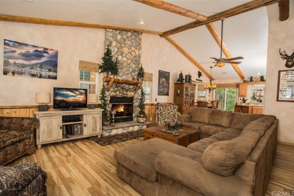 Spacious living room with high ceilings and wood burning fireplace.