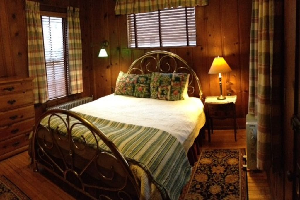 Cabin- like bedroom with queen brass bed.