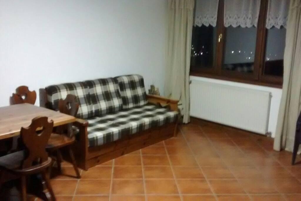 Nell'ampia sala si trova un divano letto matrimoniale, proprio vicino alla stufa a legna. Un angolo meraviglioso dove potersi godere in tranquillità il meraviglioso panorama