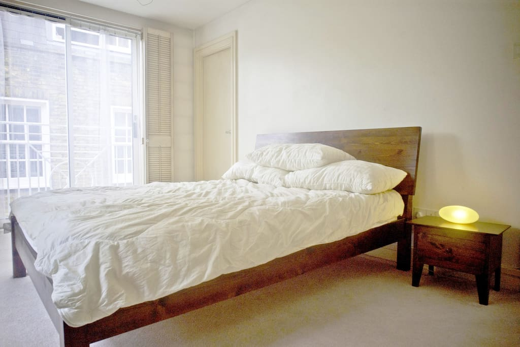 A kingsize solid wood bed handmade by British bedmaker Warren Evans, with two matching side tables.