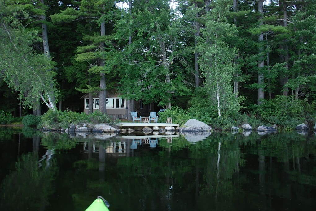 View of cabin nestled among the pines from the lake.