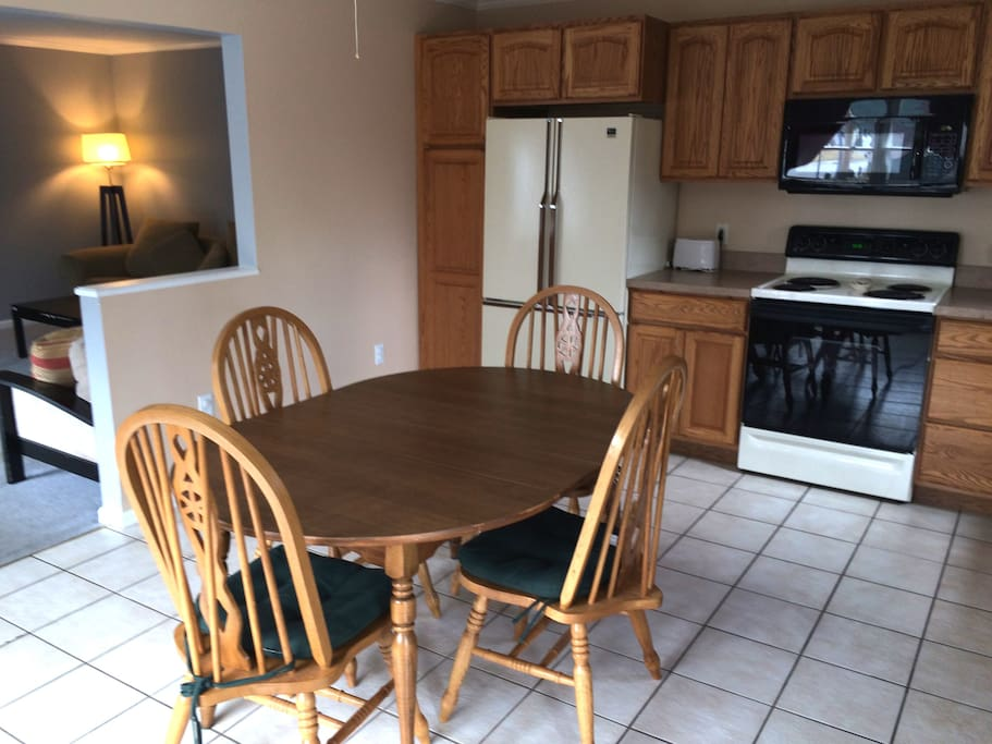 The unit features a dining area, cabinets, large microwave, electric oven and four-burner electric stove.