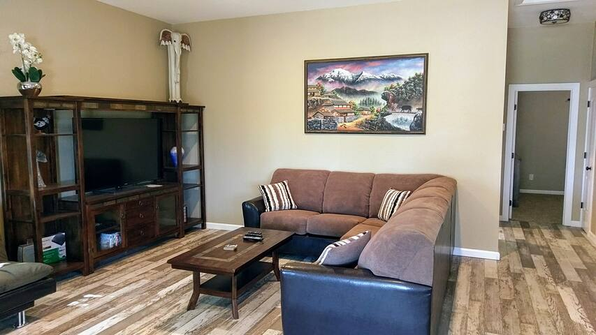 """Partial view of the living room area with 60"""" LCD TV with a decent selection of cable tv as well as a blue yay dvd player with a small selection of of popular movies. We also offer free wifi"""