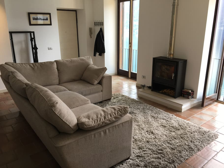 Open plan lounge with log burner and floor to ceiling shutters with stunning lake views.