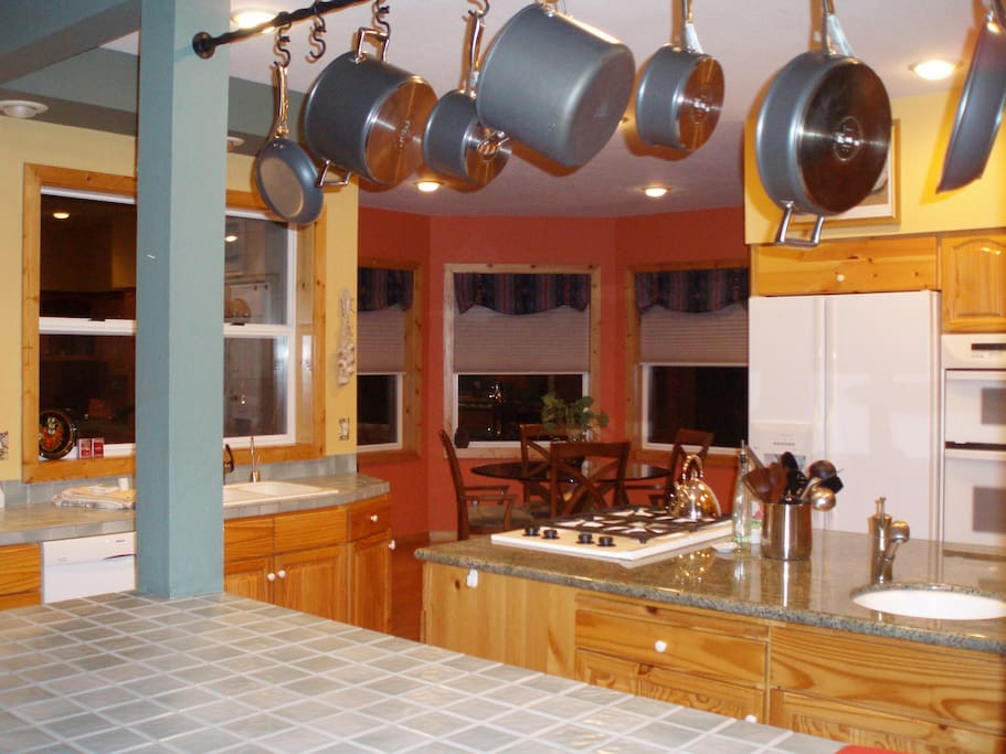 The fully equipped gourmet kitchen and adjoining Breakfast Nook in the distance. One main sink to the left under the window, and a 2nd sink on the island.