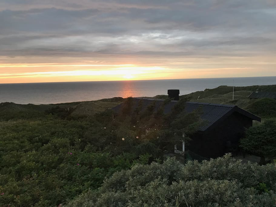 Huset ligger bag en klit med frit syn til havet