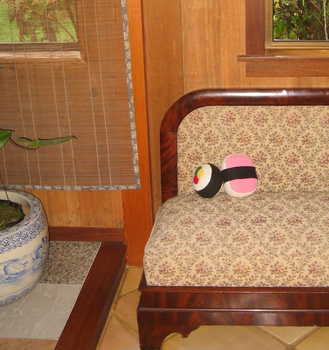 A little bench in the hallway holds sushi pillows.