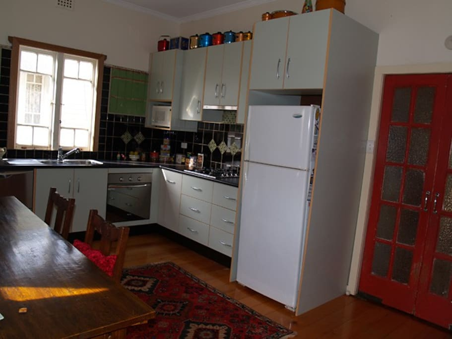 This is an older photo of the kitchen before I put in a new casement window. There is now a smaller table for 4 in the dining area and my new fridge is larger and stainless steel.
