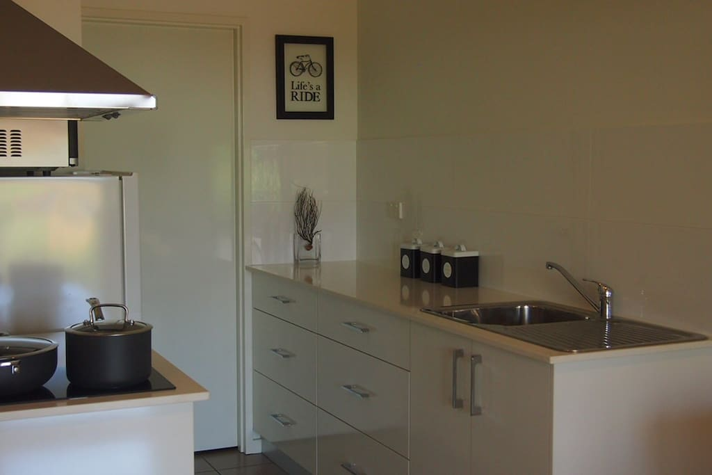 Full size modern kitchen with adjoining dining & lounge room.
