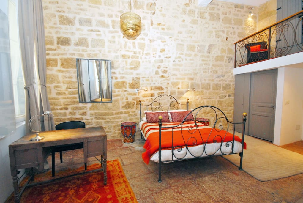 Bedroom with wrought iron bed, antique Berber carpets and desk. Huge antique carved armour and small charming balcony