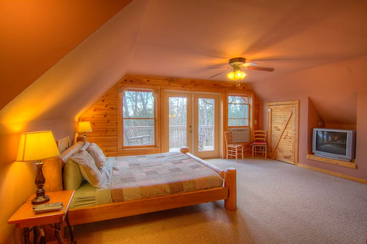 Master Bedroom with king size log bed, and it's own balcony