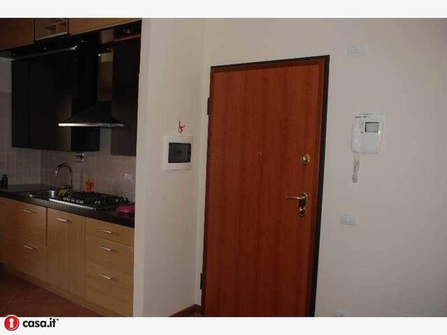 Portone di entrata con parete cucina in vista