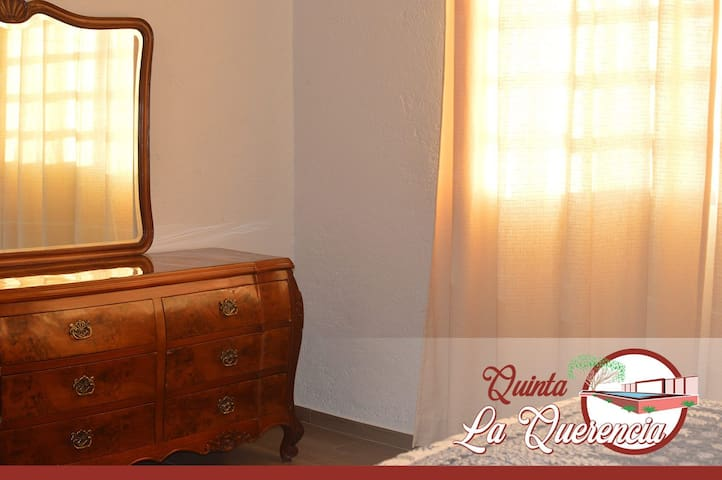 Recámara principal con cama King size, cuenta con un tocador con espejo amplio y ventana hacia el exterior.
