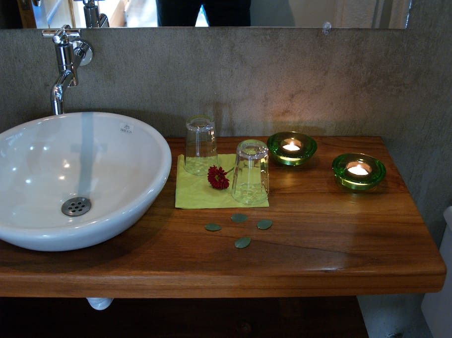 A warm teak counter adorns a bathroom.