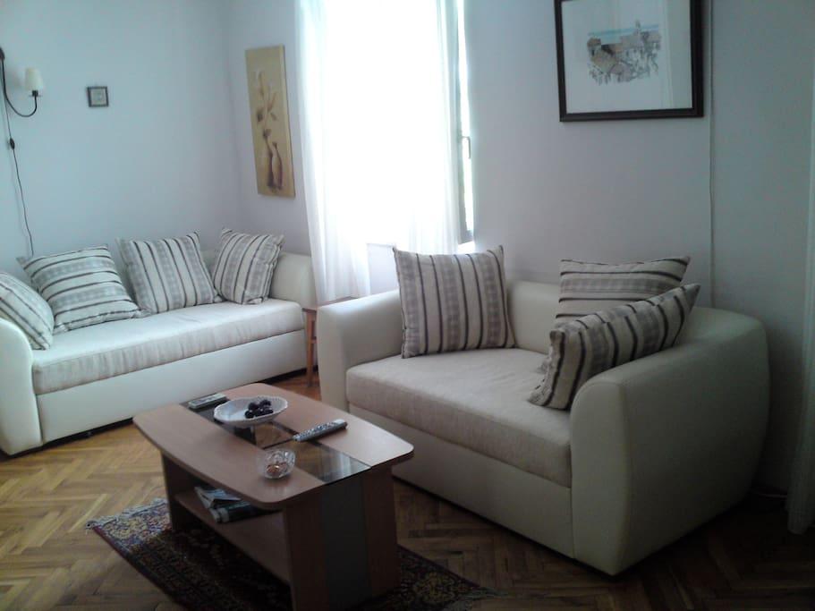 Ljust och fint vardagsrum med bäddsoffor och TV.