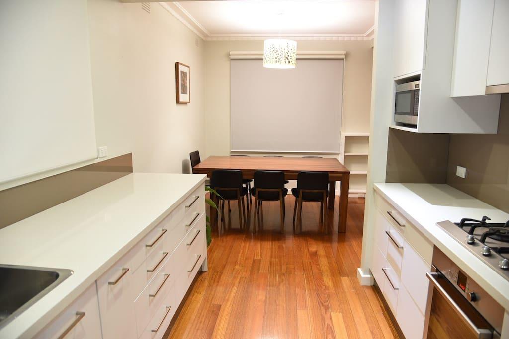 Kitchen with stone benches, dishwasher, oven, fridge, microwave ....etc