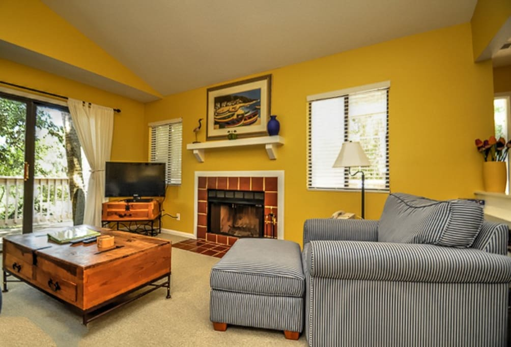 The living room has a sleeper sofa, fireplace and flat screen TV.