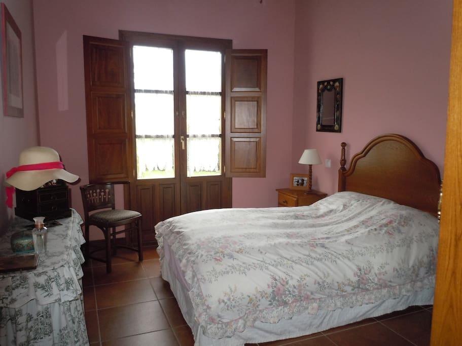 Dormitorio de cama doble con puerta-ventana directamente al jardin