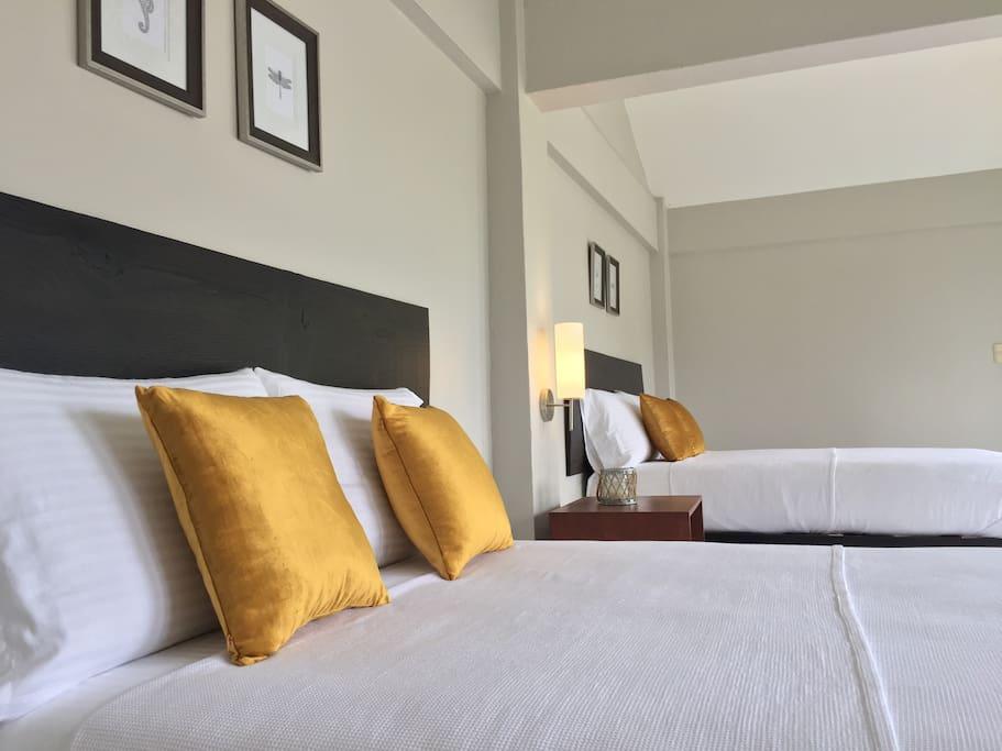 Decoración neutra y camas con ropa de algodón suave de gran calidad para un mejor descanso