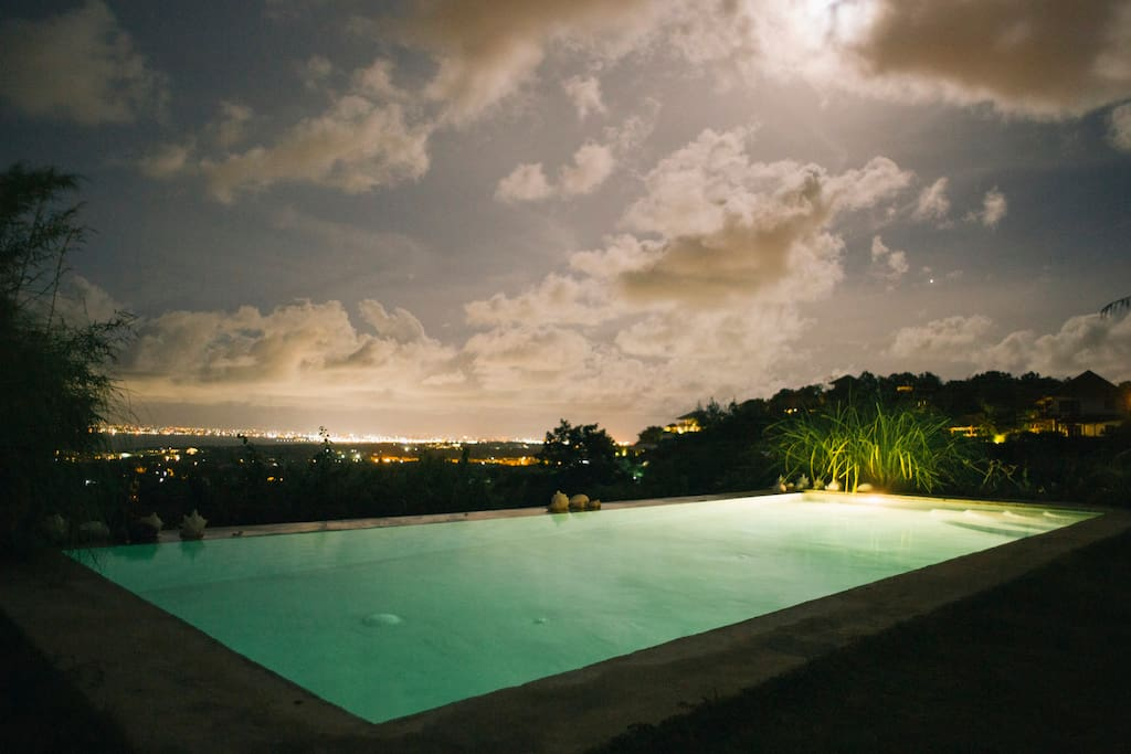 Pool overlooking the island of Bali at nigth