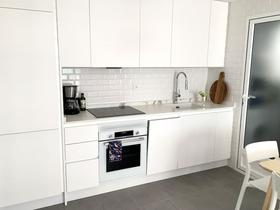 New and fully equipped kitchen with fridge, oven and dishwasher. The door from the kitchen leads to the pateo.
