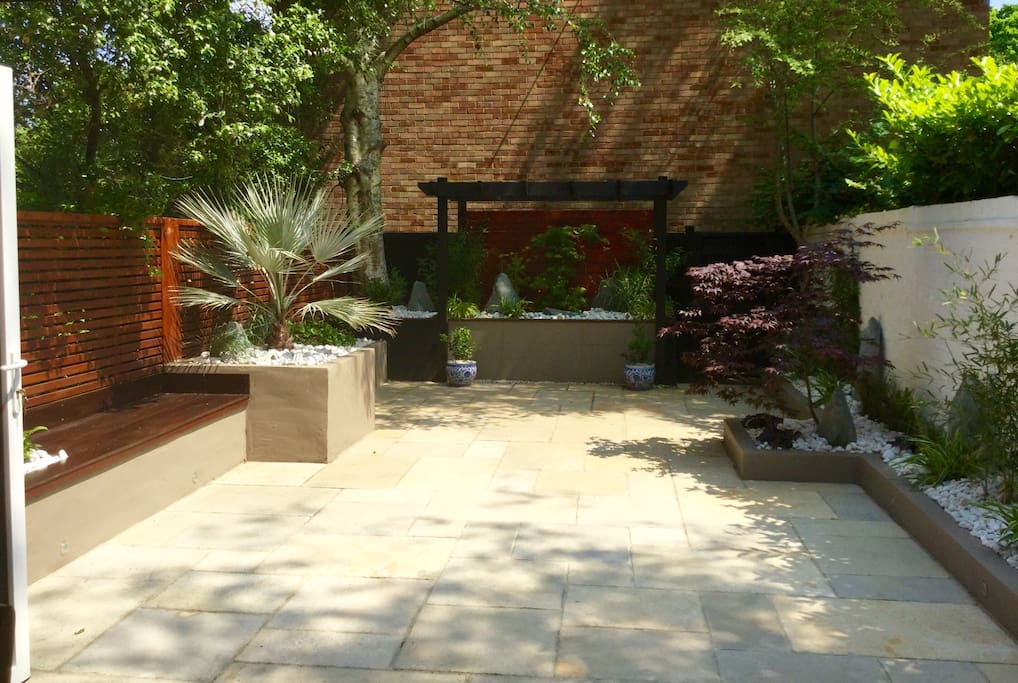 Paved garden with bench seating area - perfect for sunny days
