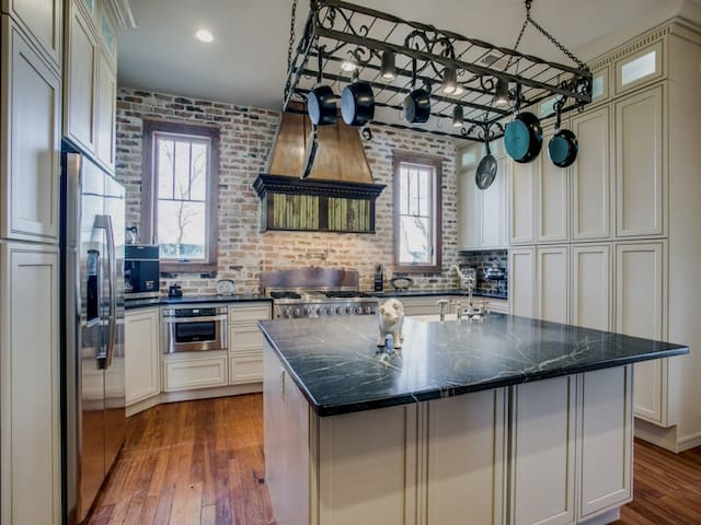 Dream Kitchen w/ commercial range / oven, soapstone countertops, excess storage and a brick back wall.