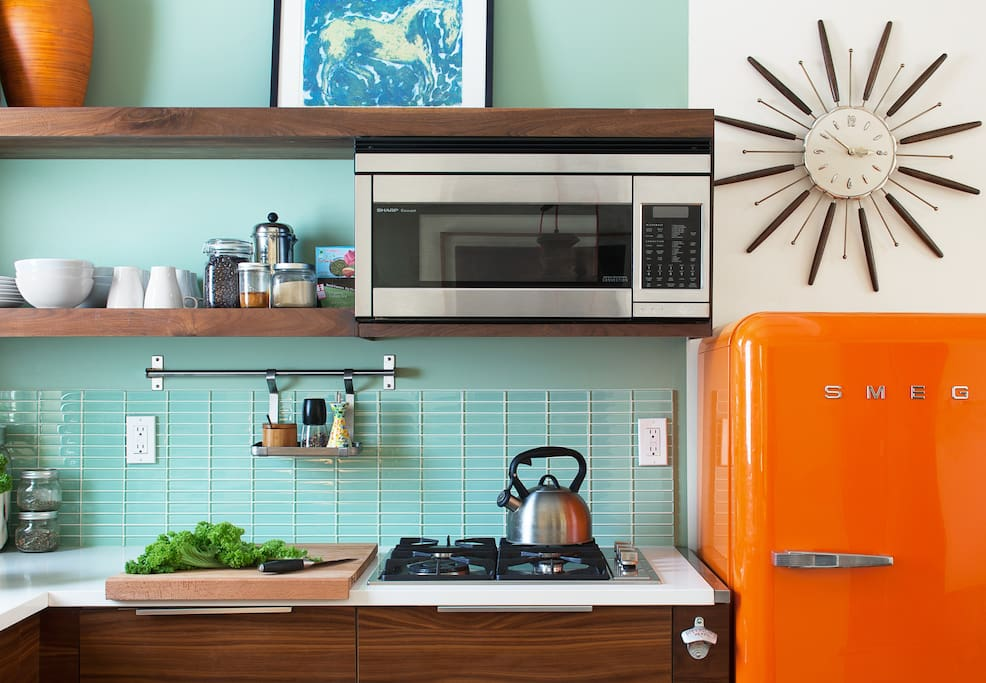 Modern and retro kitchen:  stainless appliances, quartz countertops, sexy Smeg fridge and walnut cabinets.